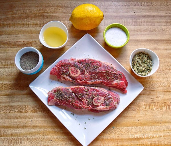 A plate of raw lamb chops surrounded by oil, lemon, and spices.