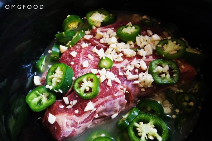A closeup of a raw beef roast, sliced jalapeños, and chopped garlic in a pot.
