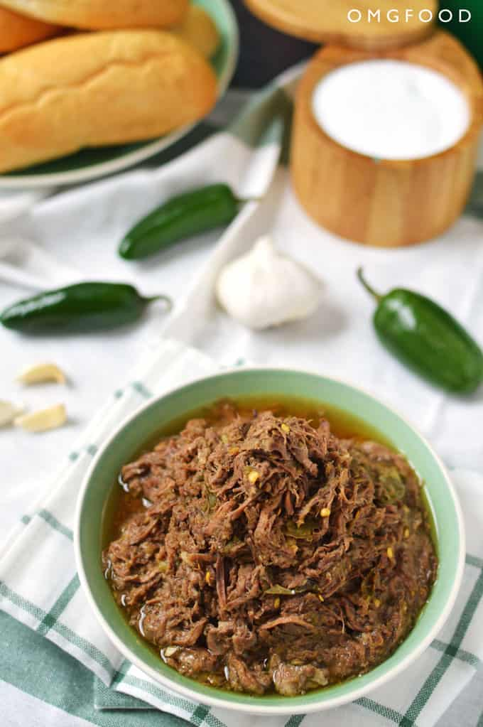 A bowl of shredded beef with jalapeños and garlic in the background.