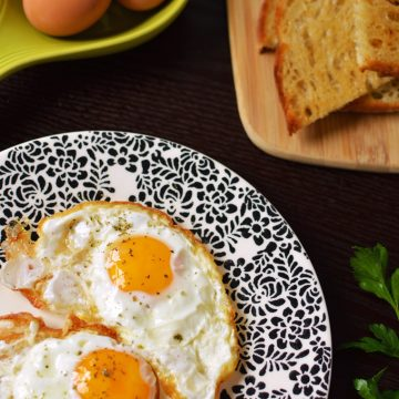 Fried eggs on a plate with toast in the background.