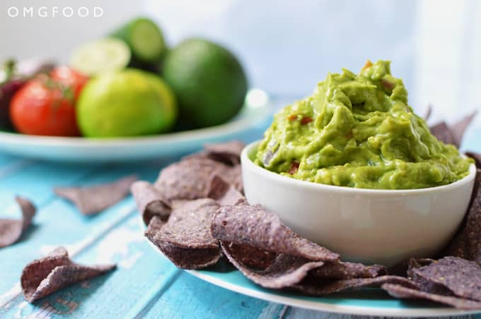 A bowl of guacamole on a plate with tortilla chips.