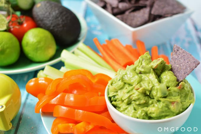 A bowl of guacamole with veggie sticks.