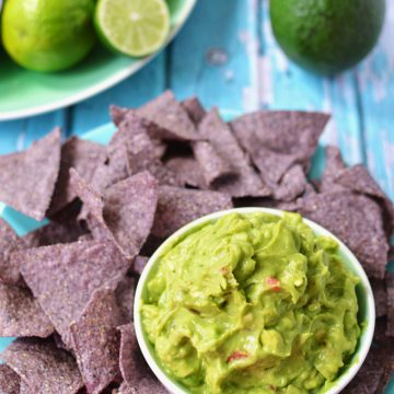 A plate of chips and bowl of guacamole on a tabletop.