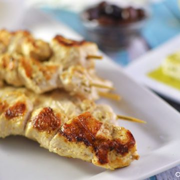 Closeup of chicken skewers on a plate.