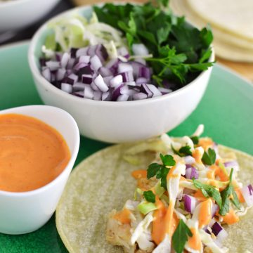 A fish taco on a plate with a side of sauce and assorted toppings.