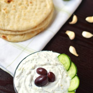 A bowl of tzatziki dip with pita bread and garlic cloves in the background.