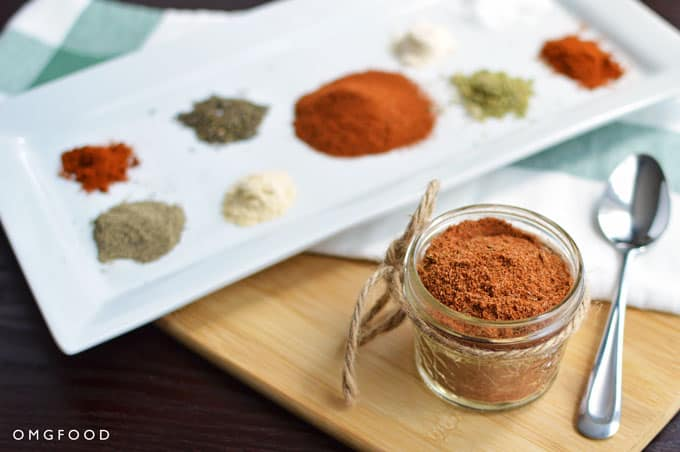 A jar of cajun spice blend with a plate of spices.