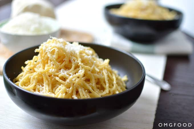 Close up of spaghetti in a bowl with grated cheese.