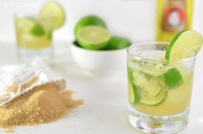 Close up of a cocktail in a drinking glass, bag of sugar, and bowl of limes on a tabletop.