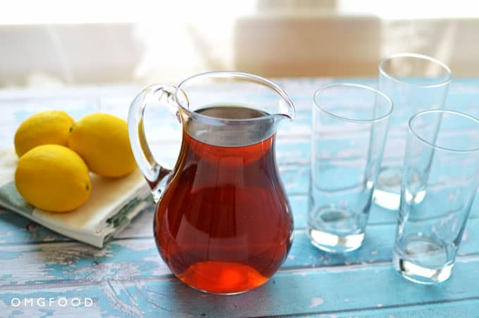 A small pitcher of iced tea next to lemons and empty drinking glasses.