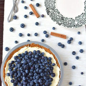 A blueberry pie on a tabletop with forks, a plate, and scattered blueberries.