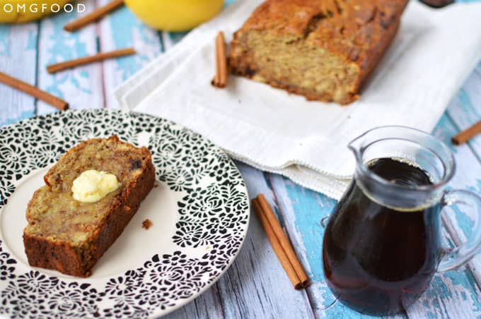 A slice of toasted banana bread with butter on a plate with a loaf of banana bread in the background.