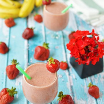 Two strawberry smoothies in glasses on a tabletop with strawberries and small vase of red flowers.