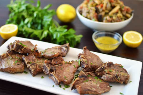 A plate of  lamb loin chops with parsley, lemon, and vegetables in the background.