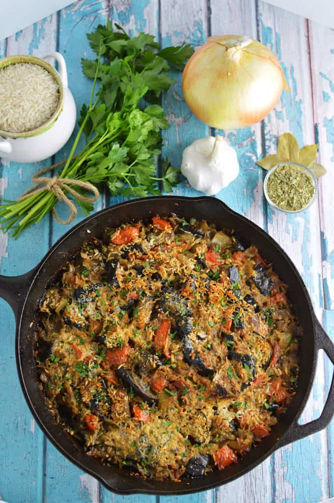 A skillet of eggplant and rice on a tabletop.