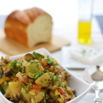A bowl of baked vegetables with bread and olive oil in the background.