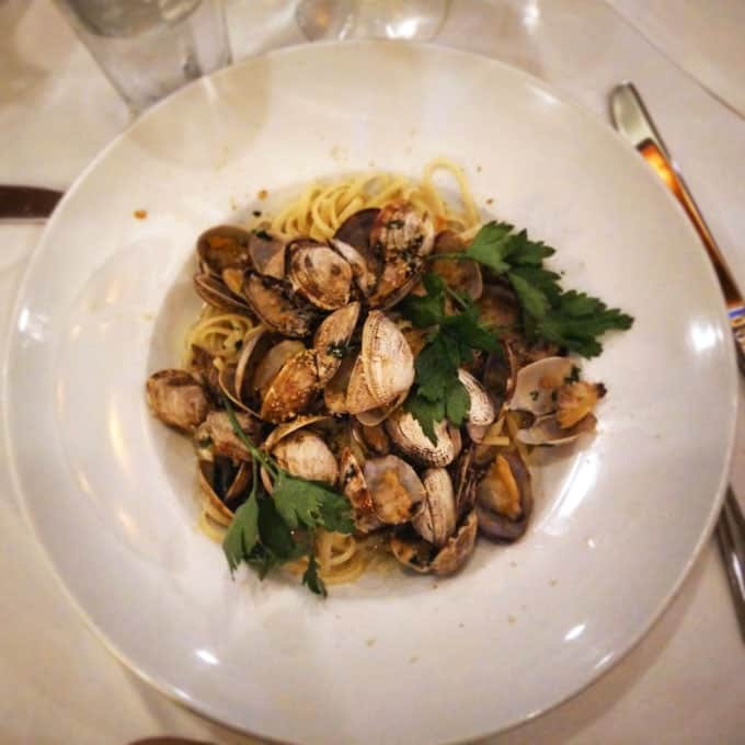 A plate of clams and pasta on a table.
