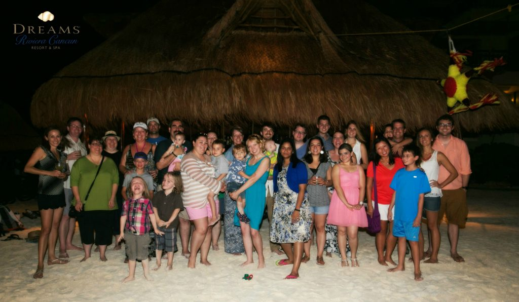 A group of people standing on a beach in front of a hut.