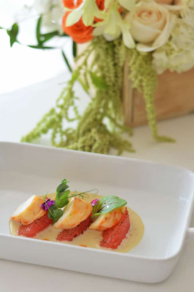 Scallops on a plate with a flower box in the background.