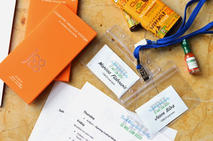Assorted papers, name tags, and chocolate bars on a tabletop.