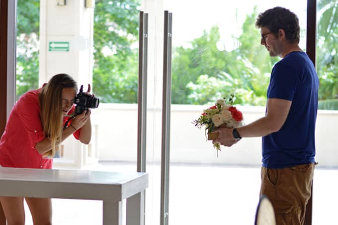 A woman taking a photo of a man holding a bouquet of flowers.