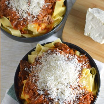 Bowls of pasta topped with meat sauce and grated cheese.