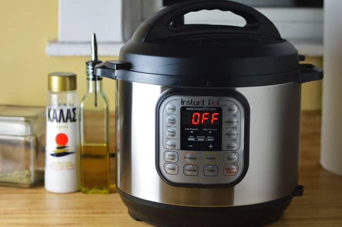 A pressure cooker next to a bottle of salt and oil.