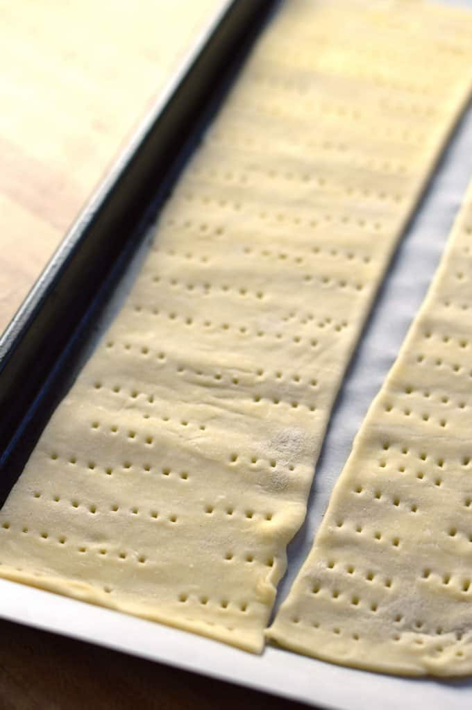 Puff pastry strips on a baking sheet.
