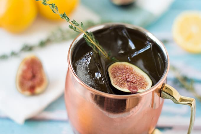A closeup of a mule cocktail in a copper mug with figs and fresh thyme.