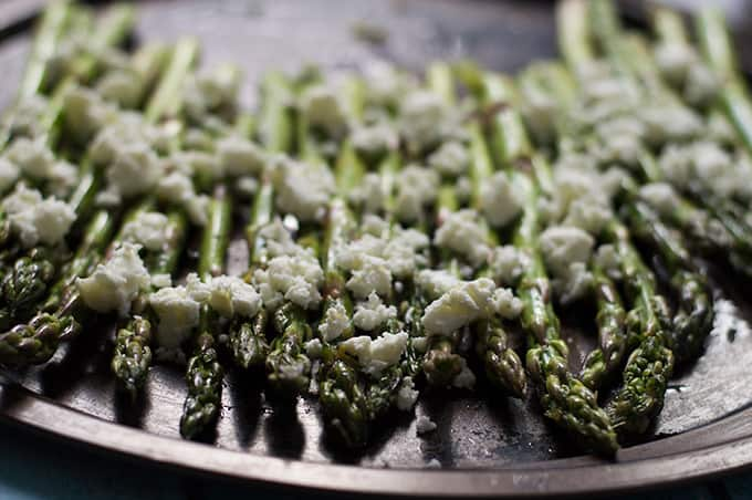 Asparagus topped with feta on a baking tray.