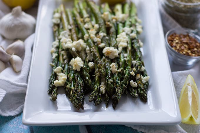Roasted asparagus topped with feta on a plate.
