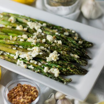 A plate of roasted asparagus topped with feta cheese.