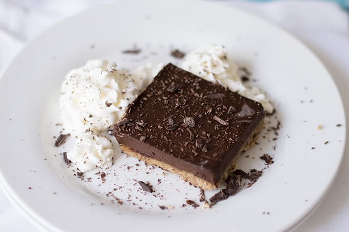 A slice of chocolate pie bar on a plate with whipped cream.