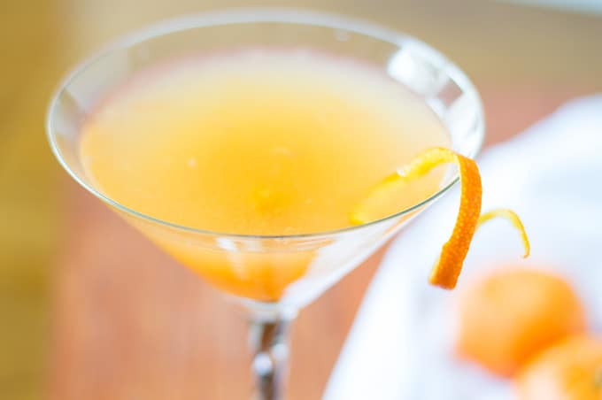 Close up of a drink in a martini glass with an orange twist.