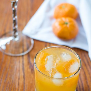 An orange drink in assorted cocktail glasses with oranges in the background.