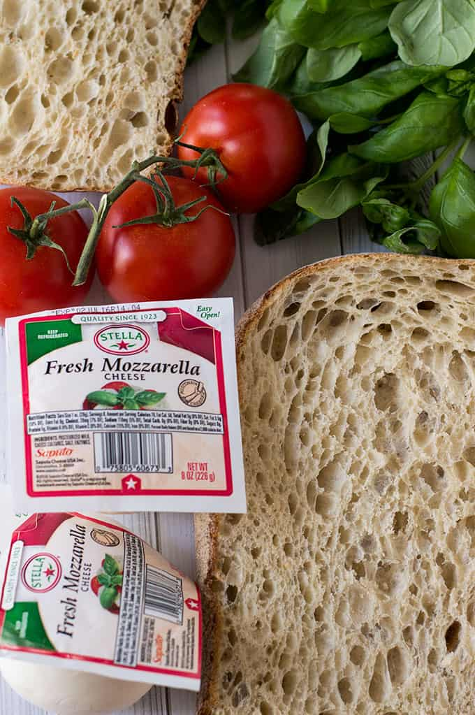 Bread, packages of fresh mozzarella cheese, tomatoes, and basil on a tabletop.