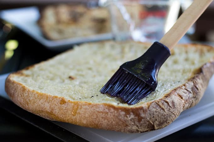 A close up of oil being brushed onto a large slice of bread.
