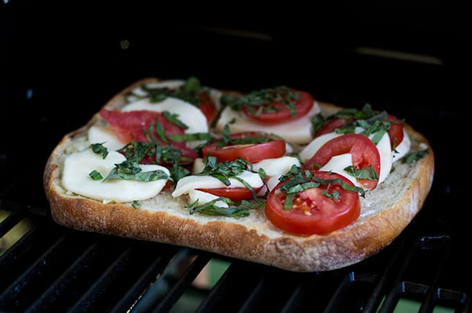 An open-faced cheese and tomato sandwich cooking on a griill.