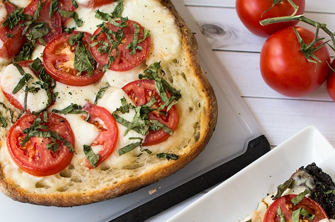 An open faced cheese and tomato  sandwich on a cutting board.