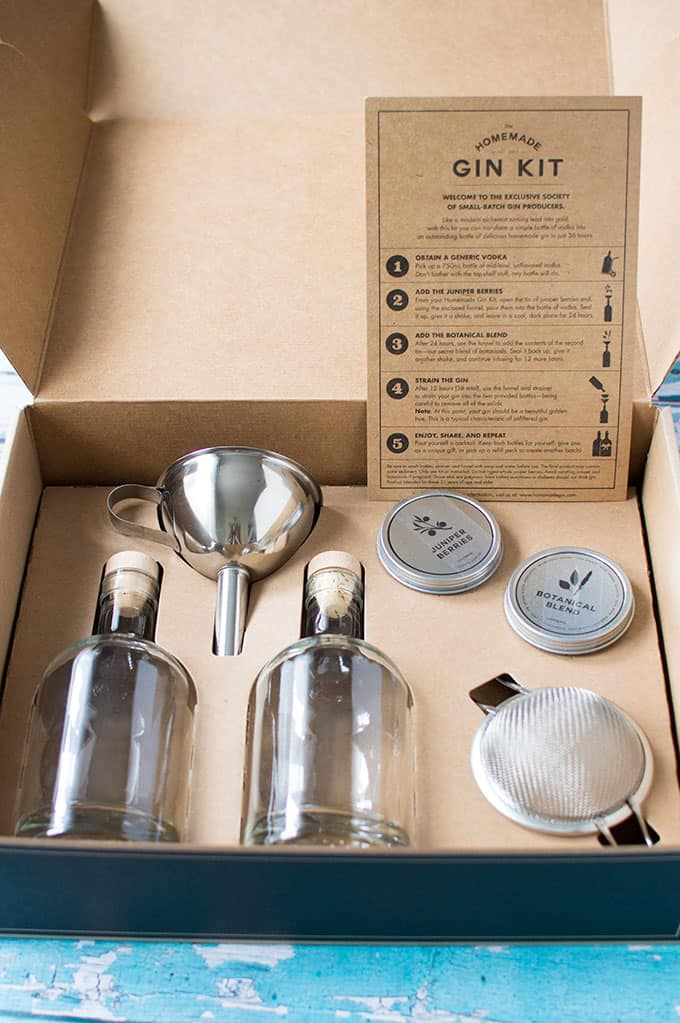 A closeup of a gin-making kit in a box, including glass bottles, a funnel, fine mesh sieve, and spices.