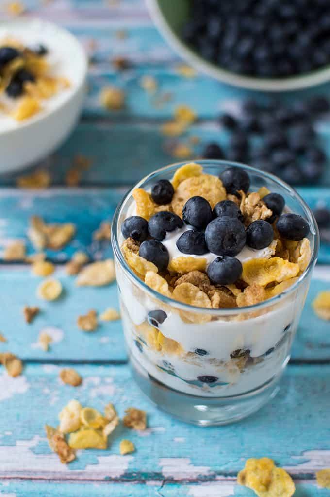 A glass bowl of layered blueberry yogurt parfait.