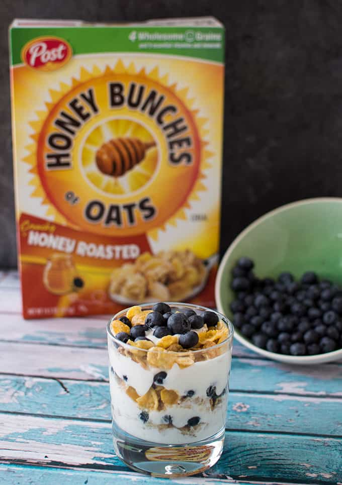 A bowl of blueberry yogurt parfait on a table with a box of cereal and bowl of blueberries.