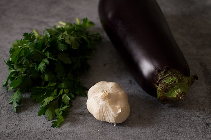 Parsley, a bulb of garlic, and an eggplant on a table.