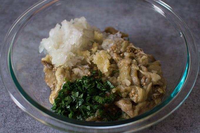 A bowl of roasted mashed eggplant, minced onion, garlic, and parsley.