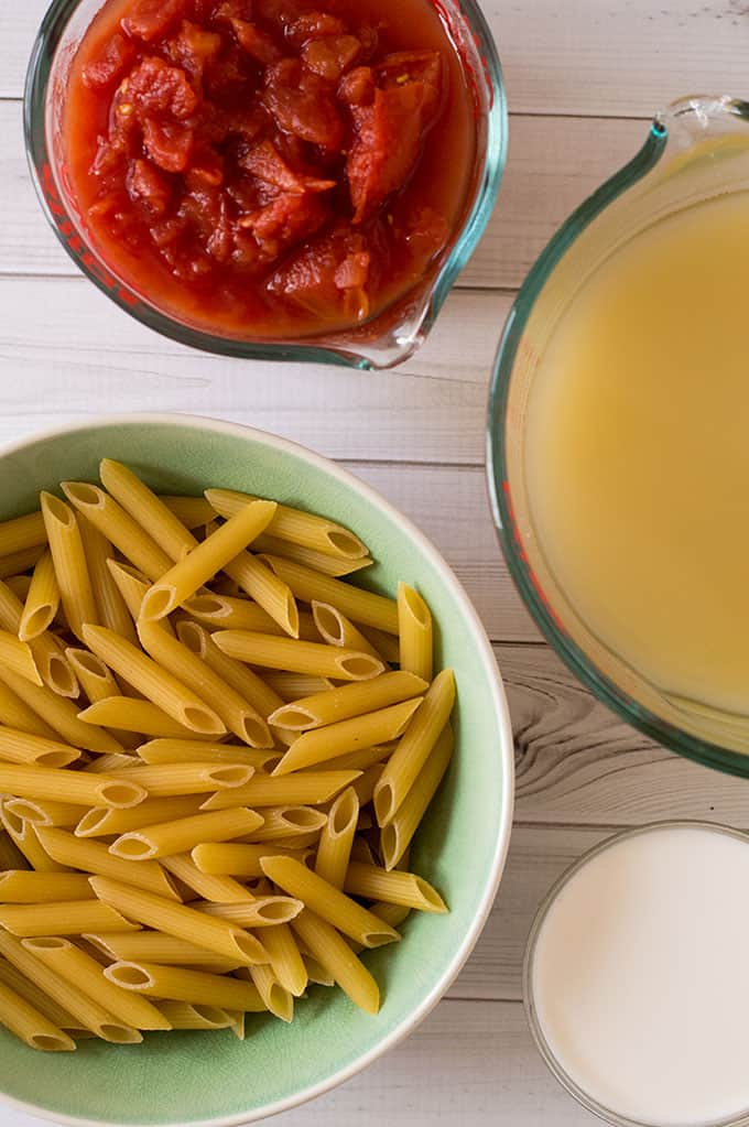 Bowls of tomatoes, chicken stock, raw penne pasta, and cream.