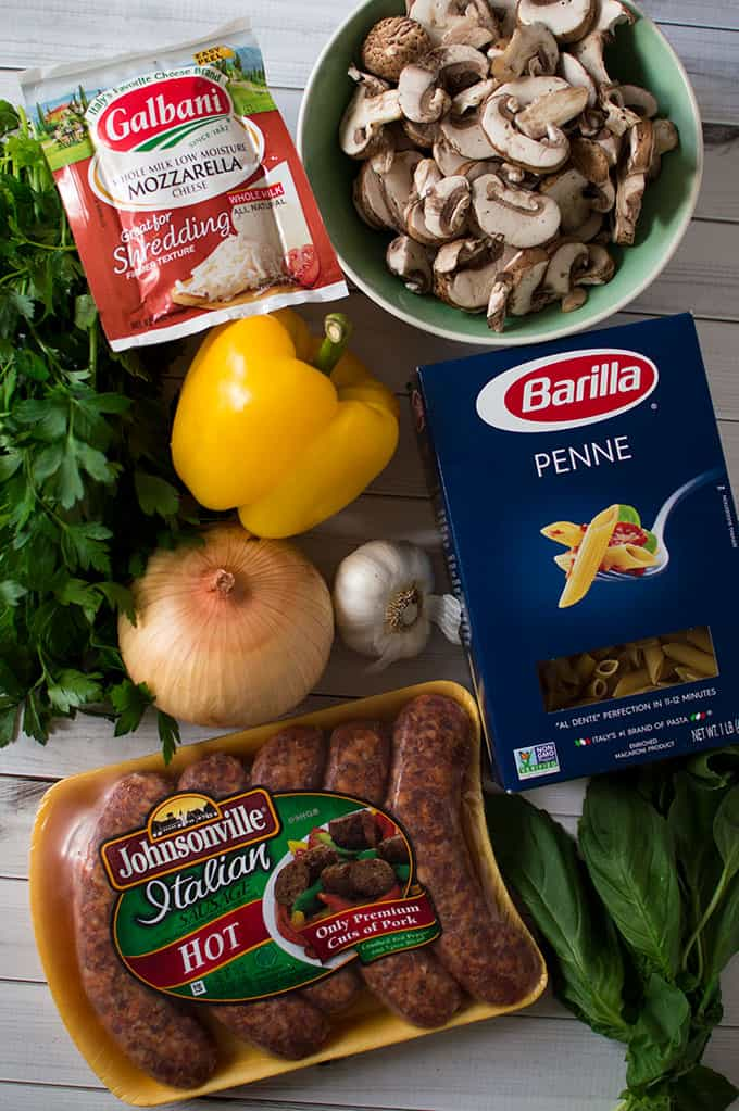 Ingredients to male one-pot creamy sausage and pasta: package of mozzarella cheese, bowl of sliced mushrooms, yellow bell pepper, whole yellow onion, bulb of garlic, box of penne pasta, package of Italian hot sausage, and fresh basil leaves.