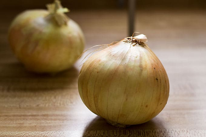 Close up of whole onions on a cutting board.