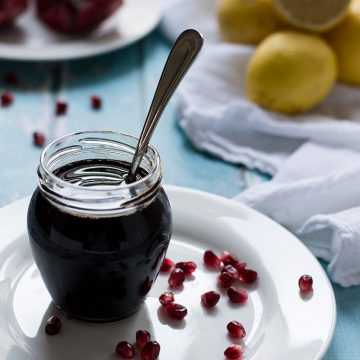 Glass jar of pomegranate molasses with a spoon inside and lemons and pomegranates in the background.