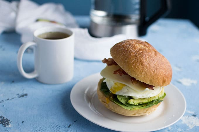 A close up of a plate with an egg sandwich and a cup of tea.