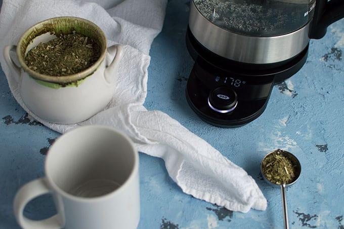 A tea kettle, empty mug, and scooped tea leaves.